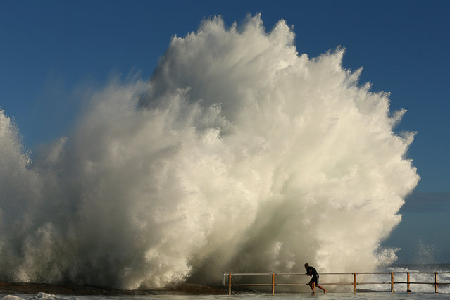 A man hangs onto the railing of North Curl Curl ocean pool after winds and rain battered Sydney last night producing large swell on January 29, 2013 in Sydney, Australia. (Photo by Cameron Spencer/Getty Images)