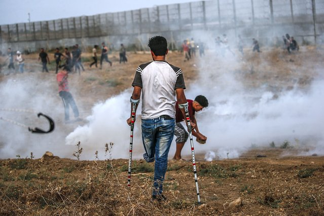 Palestinian protesters take cover from Israeli tear gas during the clahses near the border between Israel and Gaza Strip, in the eastern Gaza Strip, 21 August 2021. (Photo by Mohammed Saber/EPA/EFE)