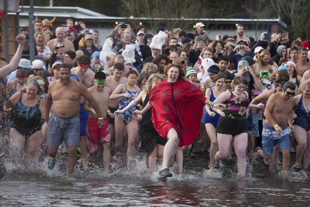 Participants run into Lake Washington during the 12th annual Polar Bear Plunge in Seattle, Washington January 1, 2014. (Photo by David Ryder/Reuters)
