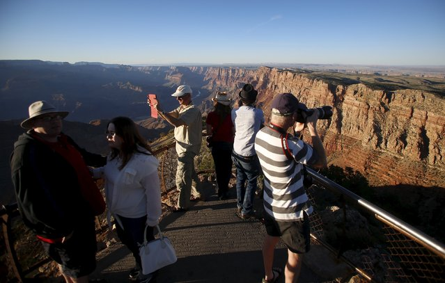 People take photos as the sun sets at the Grand Canyon National Park in northern Arizona, April 13, 2015. (Photo by Jim Urquhart/Reuters)