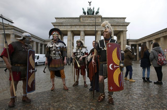 """People dressed as antient Roman soldiers walk in front the Brandenburg Gate on their way to a photo session promoting the exhibition """"Nero"""", in Berlin, Germany, February 25, 2016. The exhibition about the life of the Emperor Nero will run in the town of Trier from May 15 till October 16. (Photo by Fabrizio Bensch/Reuters)"""