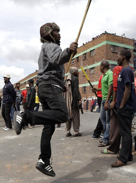 Anti-immigrant protester demonstrate outside the Jeppe hostel in Johannesburg, South Africa, Friday, April 17, 2015, where some foreigners have sought refuge.  Several shops and cars owned by foreigners were torched in downtown Johannesburg overnight in continued anti-immigrant attacks. (Photo by Themba Hadebe/AP Photo)