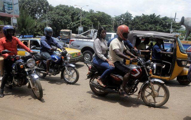 Motorcycle taxi and cars during rush hour in Conakry, Guinea Thursday, September 9, 2021. (Photo by Sunday Alamba/AP Photo)