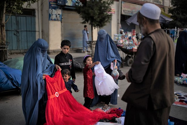 Afghan women and a girl shop for dresses at a local market in Kabul, Afghanistan, Friday, September 10, 2021. (Photo by Felipe Dana/AP Photo)