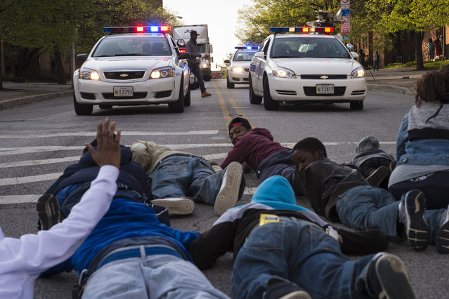 People chant and shout as they lay down to stop traffic during their march through the streets of Baltimore for Freddie Gray, a Baltimore man who died a week after suffering a spinal-cord injury while in police custody, near the site of Gray's arrest close to the corner of Presbury Street and North Mount Street in Baltimore, MD on Wednesday April 22, 2015. (Photo by Jabin Botsford/The Washington Post)