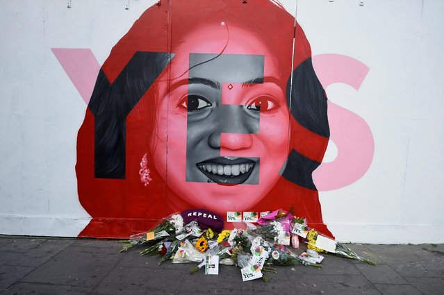 Flowers are left at the foot of a new mural of Savita Halappanavar put up on the day of the abortion referendum that repealed Ireland's strict abortion laws in Dublin, Ireland May 25, 2018. Hundreds of people left flowers and candles at a large mural of Halappanavar, the 31-year-old Indian whose death in 2012 from a septic miscarriage after being refused a termination spurred lawmakers into action. (Photo by Clodagh Kilcoyne/Reuters)