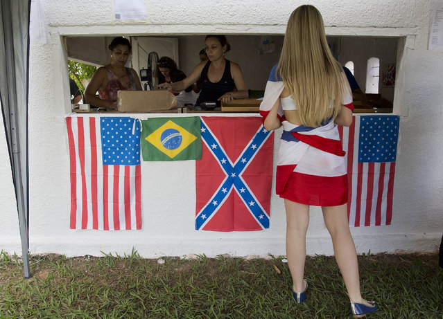 "A woman buys beverages in a cashier decorated with American, Brazilian, and Confederate flags during a party to celebrate the 150th anniversary of the end of the American Civil War in Santa Barbara d'Oeste, Brazil, Sunday, April 26, 2015. Amid food and beer stands bedecked with red-white-and-blue ribbons, extended families tuck into diet-busting barbecue and hamburger lunches as ""Dixie"" plays on a loop. (Photo by Andre Penner/AP Photo)"