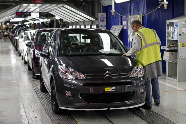 A worker looks at a Citroen C3 car in the final check area at the PSA Peugeot Citroen plant in Poissy, near Paris, April 29, 2015. PSA Peugeot Citroen said on Wednesday its revenue rose in the first quarter as the recovering French carmaker's efforts to raise prices helped offset weaker volumes. (Photo by Benoit Tessier/Reuters)