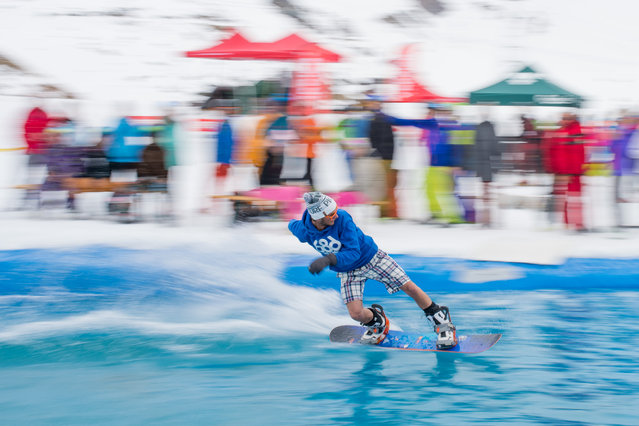 A snowboarder participates in a water sliding contest, in which athletes are gliding over a pool embedded in snow, in Verbier, southwestern Switzerland, Saturday, April 25, 2015. (Photo by Maxime Schmid/Keystone via AP Photo)