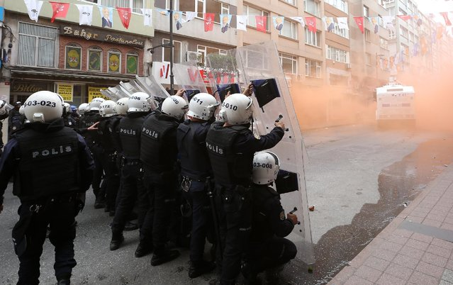 Turkish riot police officers hold their positions during clashes with demonstrators in Istanbul, Turkey, Friday, May 1, 2015. Clashes erupted between police and May Day demonstrators in Istanbul on Friday as crowds determined to defy a government ban tried to march to the city's iconic Taksim Square. Security forces pushed back demonstrators with a water cannon and tear gas. (Photo by Emrah Gurel/AP Photo)