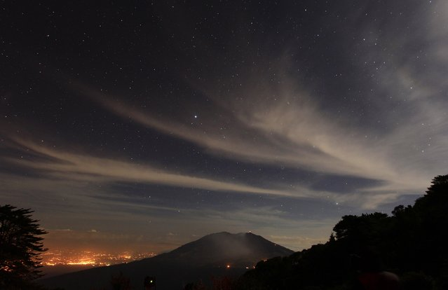 A long exposure photo shows stars above Turrialba volcano, in San Gerardo de Irazu near Turrialba March 13, 2015. Costa Rica's Turrialba volcano belched a column of gas and ash up to 3,280 feet (1 km) into the air on Thursday in its most powerful eruption in two decades, and local authorities started to evacuate residents from the surrounding area. (Photo by Juan Carlos Ulate/Reuters)