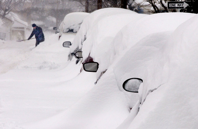 Snow covers a line of vehicles as a man digs out in Winchester, Virginia. (Photo by Scott Mason/The Winchester Star)