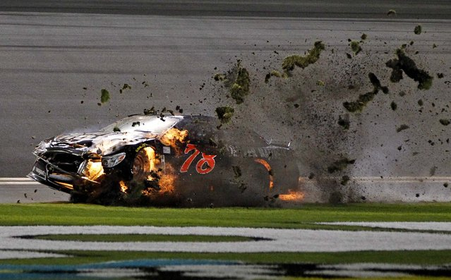 Martin Truex Jr. drives his burning car across the grass after a crash during the second of two NASCAR Sprint Cup series qualifying races at Daytona International Speedway, on February 20, 2014. (Photo by Terry Renna/Associated Press)
