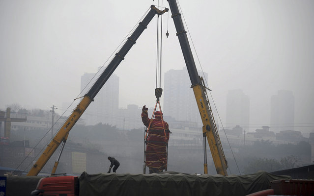 A statue of former Chinese leader Mao Zedong is prepared for removal to the Chongqing Industry Museum in southwest China's Chongqing Municipality on Tuesday Feb. 25, 2014. The sculpture was built in 1968 and erected in a state-run factory which went bankrupt later and was transformed into a logistics park. (Photo by AP Photo)