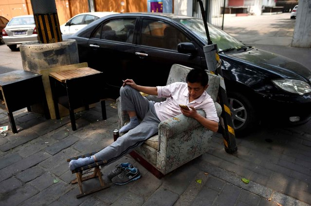 A man looks at his mobile phone while resting beside a car park in Beijing on April 30, 2015. (Photo by Greg Baker/AFP Photo)