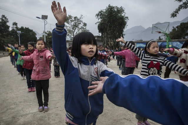 """""""Left behind"""" child Luo Hangni,11 (C), does exercises with classmates  at a local school on December 16, 2016 in Anshun, China. (Photo by Kevin Frayer/Getty Images)"""