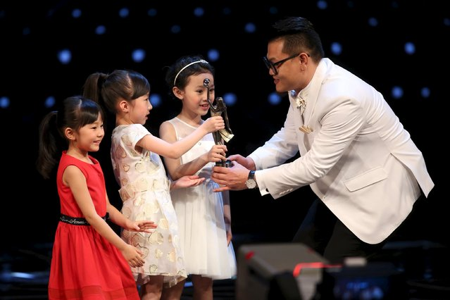 """Hong Kong actor Michael Ning receives a trophy from young actresses after winning the Best New Performer award for his role in """"Port of Call"""" at the Hong Kong Film Awards in Hong Kong, China April 3, 2016. (Photo by Reuters/Stringer)"""