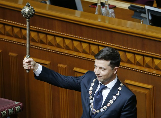 Ukrainian new President Volodymyr Zelenskiy holds the Ukrainian symbols of power during his inauguration ceremony in Kiev, Ukraine, Monday, May 20, 2019. Television star Volodymyr Zelenskiy has been sworn in as Ukraine's next president after he beat the incumbent at the polls last month. The ceremony was held at Ukrainian parliament in Kiev on Monday morning. (Photo by Efrem Lukatsky/AP Photo)