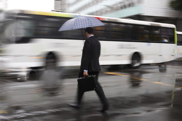 In this April 22, 2015 photo, a man walks on the street as he holds up an umbrella in downtown Rio de Janeiro, Brazil. (Photo by Leo Correa/AP Photo)