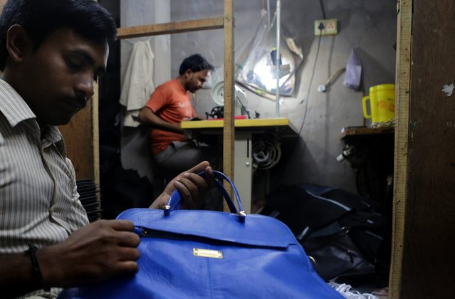 Indian bag maker Latif Muhammad (L) checks a finished leather bag while another worker is busy with stiching at a leather goods workshop at Topsia in Calcutta, eastern India, 19 November 2013. (Photo by Piyal Adhikary/EPA)