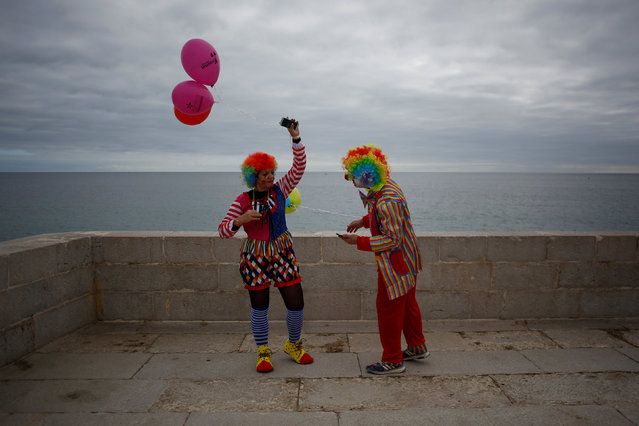 Two carnival revellers stand at Sesimbra's fortress during the clowns parade in Sesimbra village, Portugal, February 27, 2017. (Photo by Pedro Nunes/Reuters)