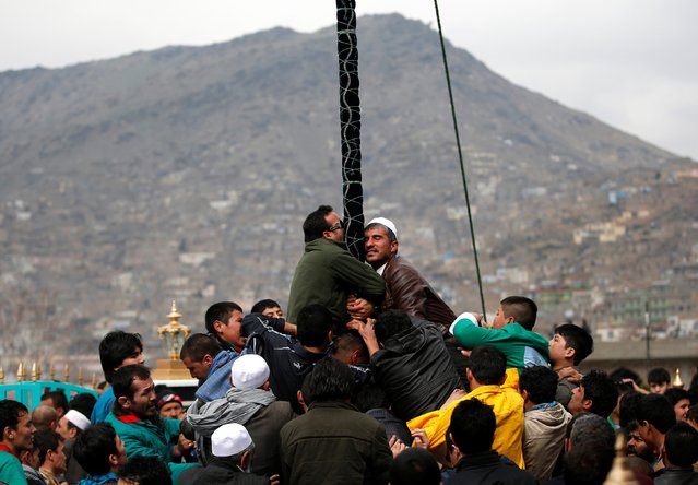 Afghans try to touch and kiss a religious flag to celebrate the Afghan New Year (Newroz) in Kabul March 21, 2014. (Photo by Ahmad Masood/Reuters)