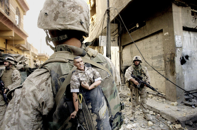 This photograph is one in a portfolio of twenty taken by eleven different Associated Press photographers throughout 2004 in Iraq.  A U.S. Marine of the 1st Division carries a mascot for good luck in his backpack as his unit pushed further into the western part of Fallujah, Iraq, Sunday, November 14, 2004. (Photo by Anja Niedringhaus/AP Photo)