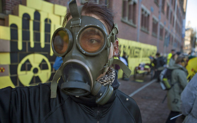 A demonstrator wears a gas mask as he gathers to protest against the Nuclear Industry Summit, which is taking place on the sidelines of the Nuclear Security summit (NSS), in Amsterdam March 24, 2014.  The Nuclear Security Summit on March 24-25, aimed at preventing nuclear terrorism, will bring together several world leaders. (Photo by Cris Toala Olivares/Reuters)