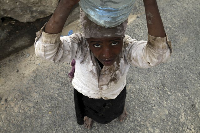 An internally displaced girl carries water on her head in the district of Khamir of Yemen's northwestern province of Amran May 9, 2015. (Photo by Mohamed al-Sayaghi/Reuters)