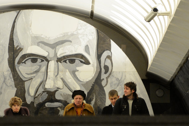 Subway passengers walk at the Dostoyevskaya metro station in Moscow, on November 15, 2012. A portrait of Fyodor Dostoyevsky, one of the highly regarded Russian writers, is seen in the background. (Photo by Kirill Kudryavtsev/AFP Photo)