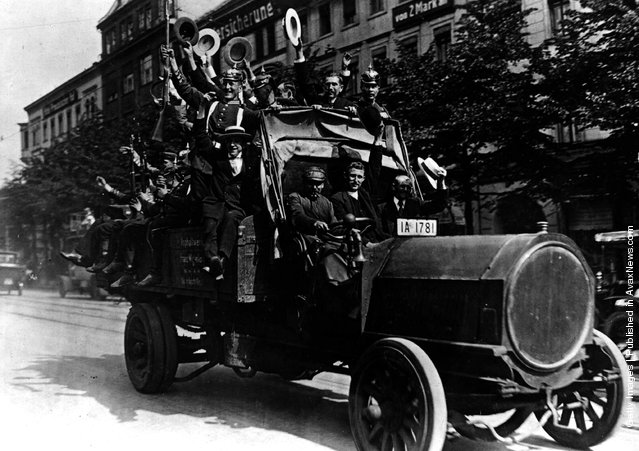 1914: German army Reservists waving and cheering as they rush to join