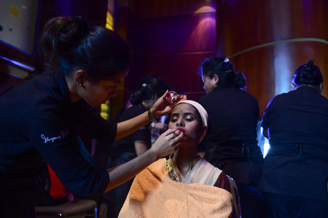 "A woman, a Bangladeshi acid attack survivor, has makeup applied backstage prior to the fashion show ""Beauty Redefined"" by designer Bibi Russell featuring acid attack survivors in Dhaka on March 7, 2017. (Photo by AFP Photo/Stringer)"