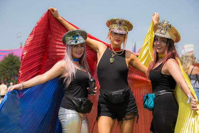 Festival goers pose for photographers on the third day of Glastonbury Festival at Worthy Farm, Somerset, England, Friday, June 28, 2019. Temperatures are expected to soar over the weekend as a heatwave hits parts of Europe, while the festival runs for five days and is one of the largest events of its kind in the world. (Photo by Joel C. Ryan/Invision/AP Photo)