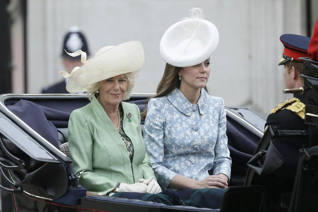 """Britain's Kate, Duchess of Cambridge, right, and the Duchess of Cornwall ride in a carriage during the Trooping The Colour parade at Buckingham Palace, in London, Saturday, June 13, 2015. Hundreds of soldiers in ceremonial dress have marched in London in the annual Trooping the Color parade to mark the official birthday of Queen Elizabeth II. The Trooping the Color tradition originates from preparations for battle, when flags were carried or """"trooped"""" down the rank for soldiers to see. (AP Photo/Tim Ireland)"""