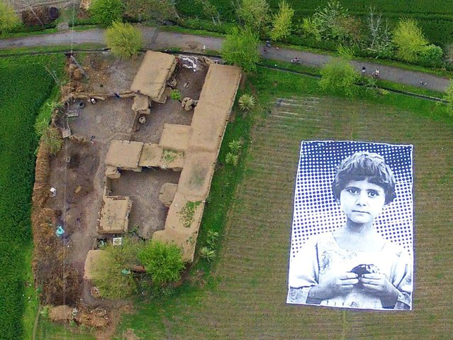 "In this undated handout photograph from the ""Inside Out Project"", a poster bearing the image of a Pakistani girl whose parents, lawyers say, were killed in a drone strike, lies in a field at an undisclosed location in the northwestern Khyber-Pakhtunkhwa province. (Photo by AFP Photo)"