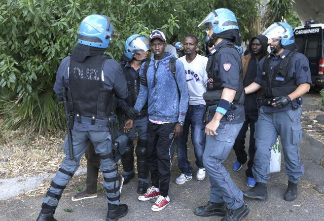 Migrants are evacuated by Italian police at the Franco-Italian border near Menton, southeastern France, Tuesday, June 16, 2015. Some 150 migrants, principally from Eritrea and Sudan, have been trying since last Friday to cross the border from Italy but have been blocked by French and Italian police. (AP Photo/Lionel Cironneau)