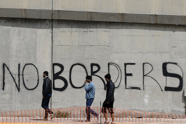Migrants walk past graffiti at the port city of  Piraeus, Greece on Monday, April 25, 2016. Around 3,500 migrants remain in Piraeus using tents, a warehouse and a terminal passenger building for shelter, as over 50,000 stranded refugees and migrants remain in the country. (Photo by Thanassis Stavrakis/AP Photo)