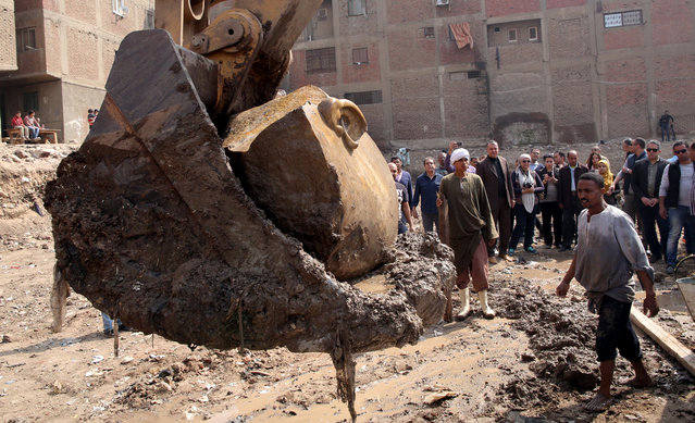 Egyptian workers lift with an excavator parts of a statue for restoration after it was unearthed at Souq al-Khamis district, at al-Matareya area, Cairo, Egypt, 09 March 2017. According to the Ministry of Antiquities, a German-Egyptian archaeological mission found in parts two 19th dynasty royal statues in the vicinity of King Ramses II temple in ancient Heliopolis. The first is an 80cm tall bust of King Seti II carved in limestone, while the second is eight meters tall carved in quartzite. There were no engravings on the latter, however discovering it at the entrance of King Ramses II temple suggests that it could belong to him. (Photo by Khaled Elfiqi/EPA)