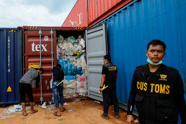 """This picture taken on June 15, 2019 shows Indonesian customs officers from the local environment office examining one of 65 containers full of imported plastic rubbish, at the Batu Ampar port in Batam. Indonesia returned five other containers of rubbish to the United States and will not become a """"dumping ground"""", officials said on June 15, the latest Southeast Asian country to return imported waste. (Photo by Andaru/AFP Photo)"""