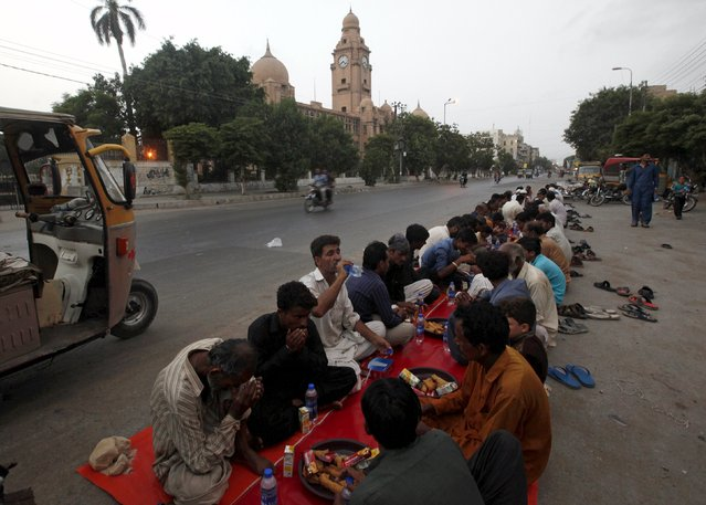 People break their fast during the holy month of Ramadan along a road in Karachi, Pakistan, June 28, 2015. (Photo by Akhtar Soomro/Reuters)