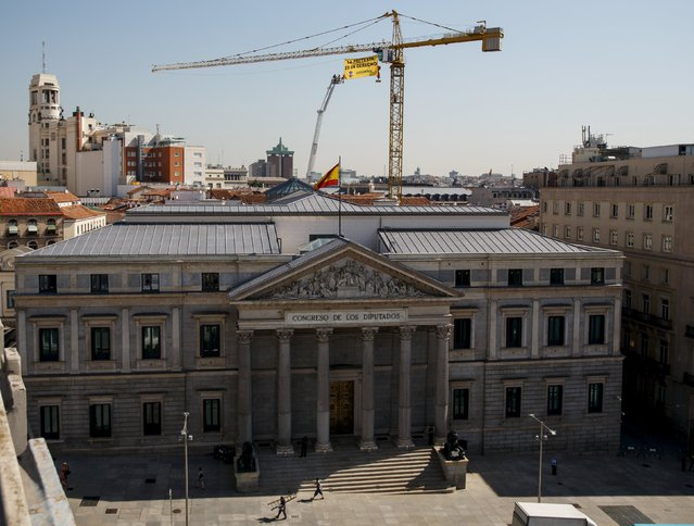 """Greenpeace activists hang with a banner from a crane above the Spanish parliament in Madrid, Spain, June 30, 2015. Spanish government's new security law, which toughens fines for unauthorised street protests, comes into effect July1. Critics consider it a violation of the right to protest and a limit to free expression and have labelled it """"Ley Mordaza"""" (Gag Law). Banner reads """"Protest is a right"""". (Photo by Andrea Comas/Reuters)"""