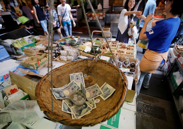 Coins and banknotes that are used for change are seen in a bamboo basket at a greengrocer in Tokyo, Japan on August 22, 2013. (Photo by Toru Hanai/Reuters)