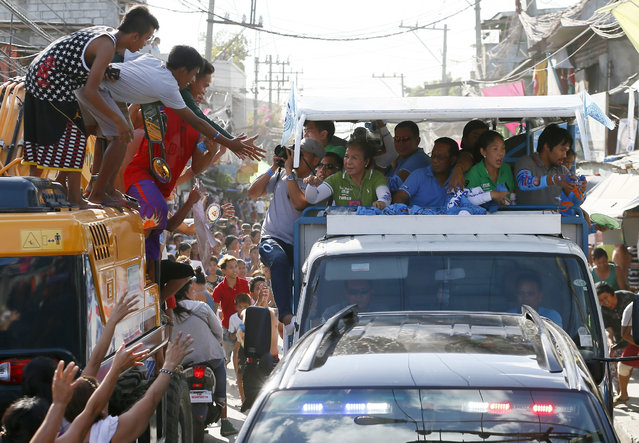 Presidential candidate Vice-president Jejomar Binay, center, and Congressman Manny Pacquiao, right, who is running for senator in Monday's national elections, throw souvenir t-shirts, candies and wrist bands to supporters during their campaign sortie in Navotas north of Manila, Philippines Friday, May 6, 2016. (Photo by Bullit Marquez/AP Photo)
