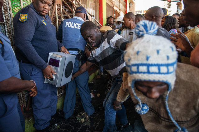 Members of the South African Police Service try to halt looters to enter a shop during a riot in the Johannesburg suburb of Turffontein on September 2, 2019 as angry protesters loot alleged foreign-owned shops today in a new wave of violence targeting foreign nationals. (Photo by Michele Spatari/AFP Photo)