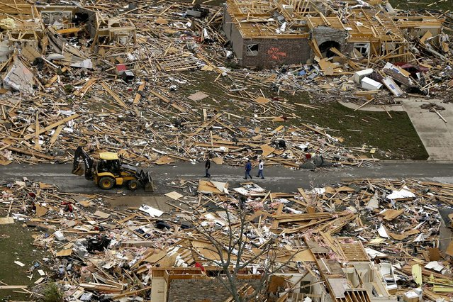 People walk between two destroyed houses in Mayflower, Arkansas on Monday. (Photo by Danny Johnston/Associated Press)