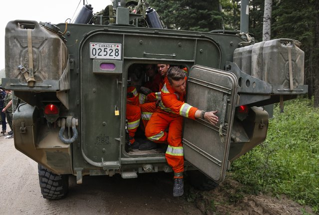 Members of the Canadian Forces prepare to head out to look for hotspots from wildfires near Montreal Lake, Saskatchewan, Thursday, July 9, 2015. Large wildfires raging across Canada have contributed to a smoky haze lingering above the Western U.S., blazes fueled by the familiar hot, and dry conditions that have turned much of the region into a tinderbox. (Photo by Jeff McIntosh/The Canadian Press via AP Photo)