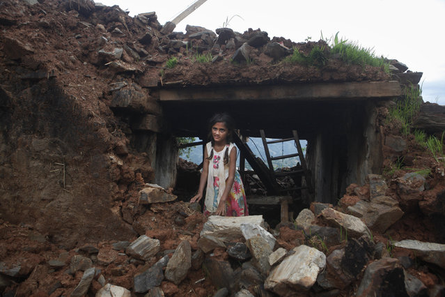 Salina Dahal, who reportedly had a brain surgery soon after the devastating earthquake by CNN's medical correspondent Dr. Sanjay Gupta, poses for a photograph outside her home in Dahal Village, 48 kilometers (30 miles) east of Kathmandu, Nepal, Friday, July 10, 2015. CNN said on Thursday that it is working to verify the identity of the Nepalese patient following a published report that Dahal never had a surgery. (Photo by Niranjan Shrestha/AP Photo)