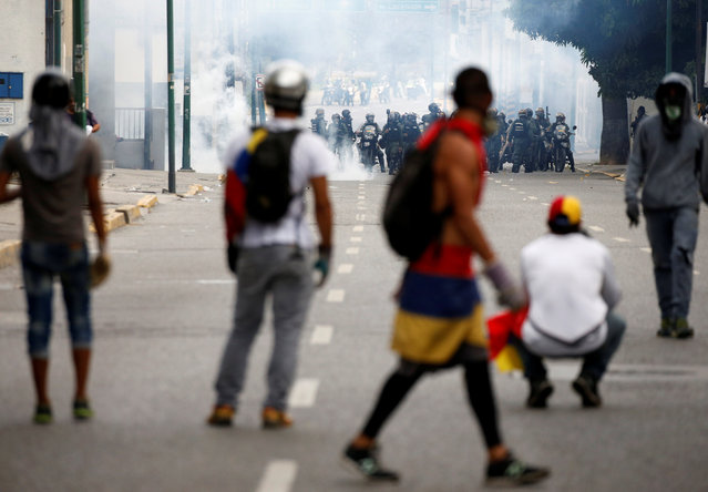 """Demonstrators clash with riot police during the so-called """"mother of all marches"""" against Venezuela's President Nicolas Maduro in Caracas, Venezuela April 19, 2017. (Photo by Carlos Garcia Rawlins/Reuters)"""