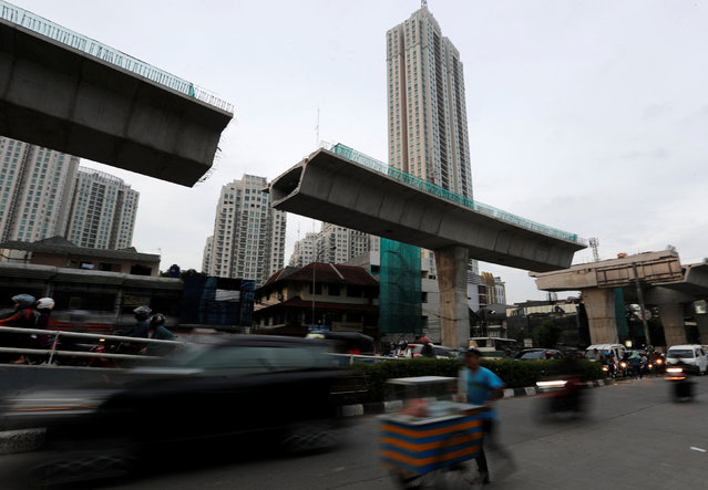 A street vendor push his cart under a flyover construction in Jakarta, Indonesia, May 11, 2016. (Photo by Reuters/Beawiharta)