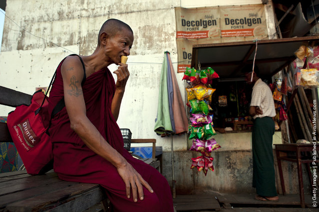 A Burmese monk eats an ice cream cone